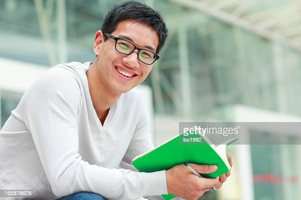 happy male college student reading book