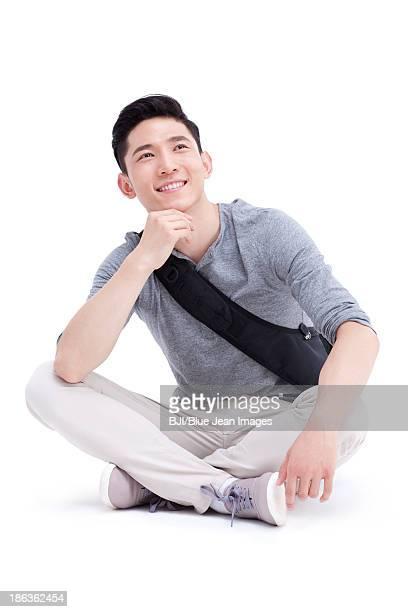 Happy male college student sitting cross-legged