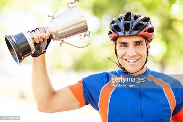 Heureux mâle cycliste tenant un trophée