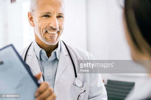 Happy male doctor discussing with female colleague