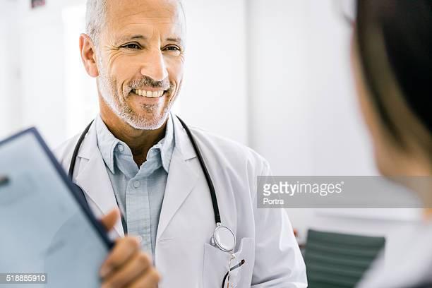 Glücklich männlichen Arzt mit weiblichen Kollegen diskutieren.