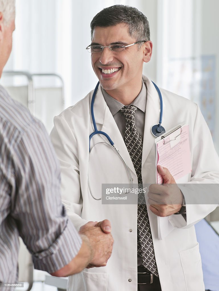 Happy male doctor greeting a patient at hospital : Stock Photo