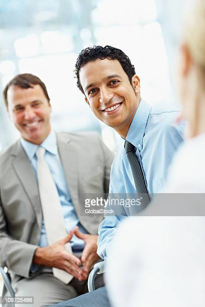 Happy male executive with colleagues in office