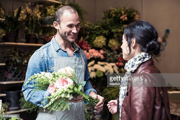 Happy male florist giving bouquet of flowers to customer at shop