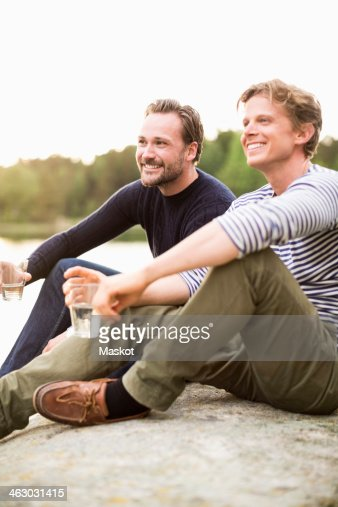 Happy male friends holding glasses of water while sitting on rock