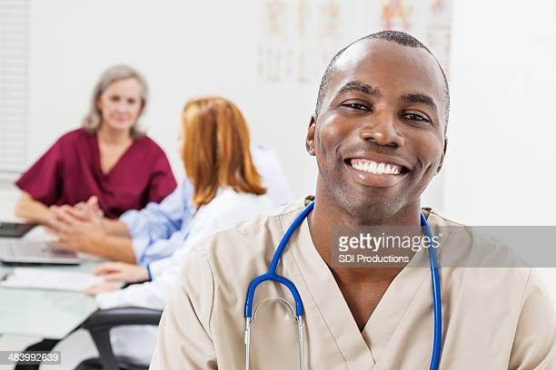 Hombre feliz sonriente enfermera hospital durante la reunión de personal