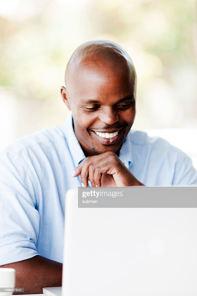Happy male working on laptop : Stock Photo