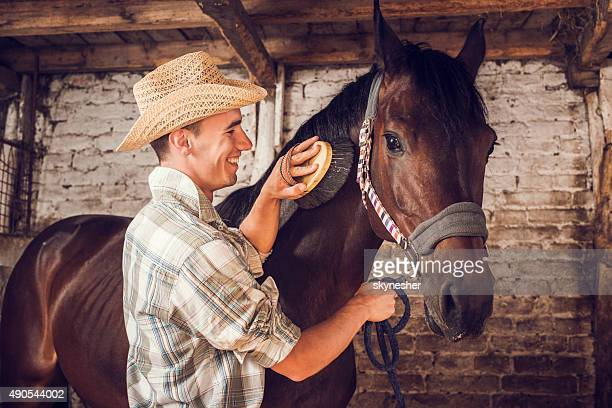 Happy man brushing his horse in a barn.
