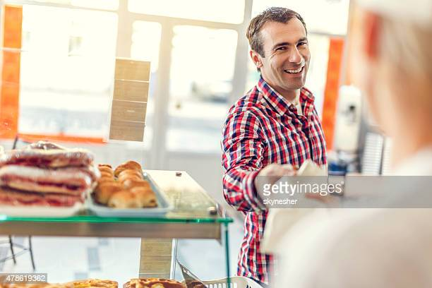 Happy man buying pastry in bakery.
