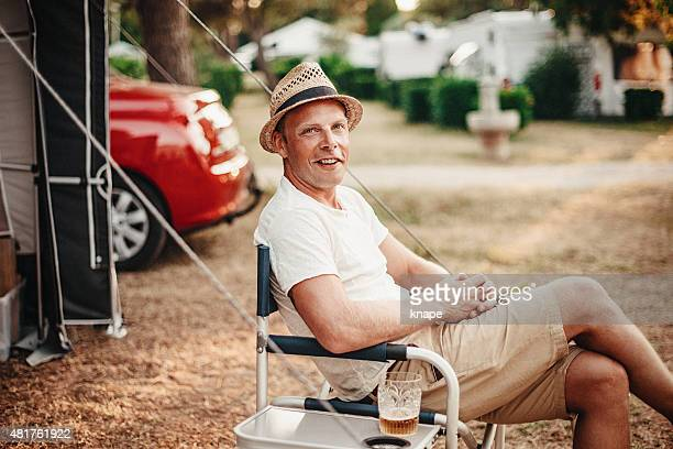 Happy man camping in his caravan at camping pitch