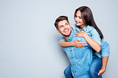 Happy  man carrying his girlfriend on the back on gray background