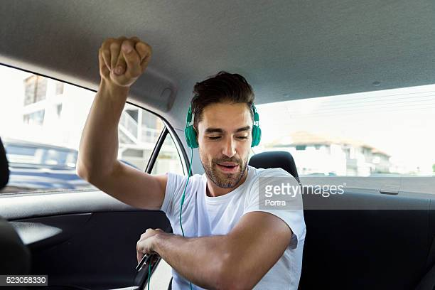 Happy man dancing while listening to music in car
