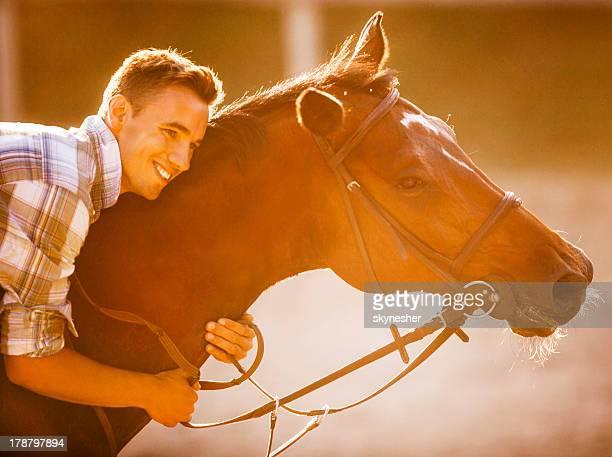 Happy man embracing his horse.