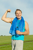 color portrait of a happy laughing man in his forties playfully flexing his muscles for the camera.He is wearing a blue tank top and grey shorts.