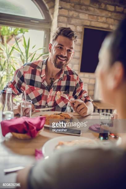Hombre feliz almorzar con su novia en un restaurante.