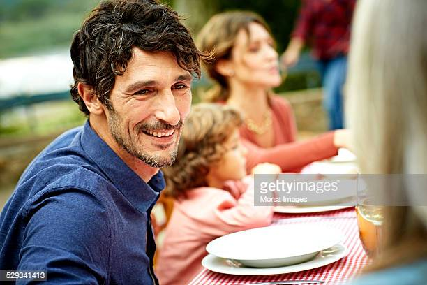 Happy man having meal with family in yard