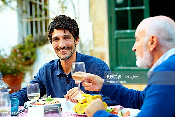 Happy man having meal with father at outdoor table