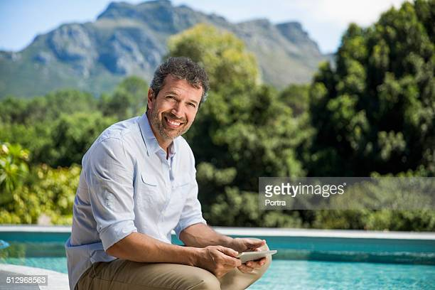 Happy man holding digital tablet at poolside