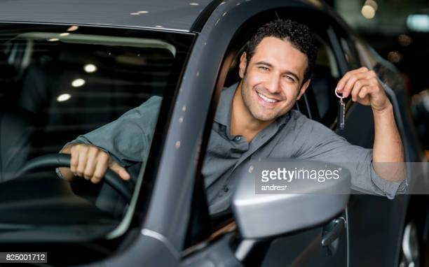 Happy man holding keys of a car at the dealership