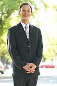 A happy man in a suit standing on the street.