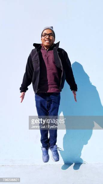 Happy Man Levitating Against Wall During Sunny Day