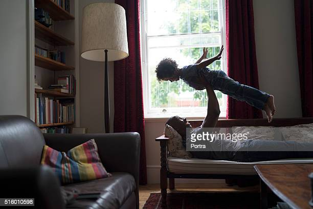 Happy man lifting daughter while lying on seat