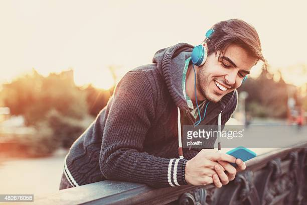 Happy man listening music and texting outdoors