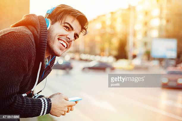Happy man listening music outdoors