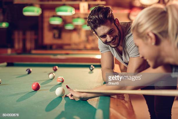Happy man looking at his girlfriend playing billiard.