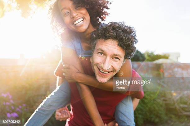 Happy man piggybacking female friend in yard