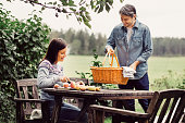 Happy man placing basket on table while woman cutting apples at organic farm