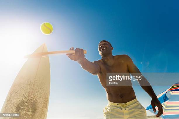 Happy man playing tennis against clear blue sky
