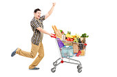 'Full length portrait of a happy man pushing a shopping cart, isolated on white background'