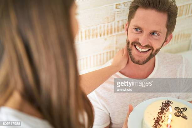 happy man receiving birthday wishes and cake from his girlfriend