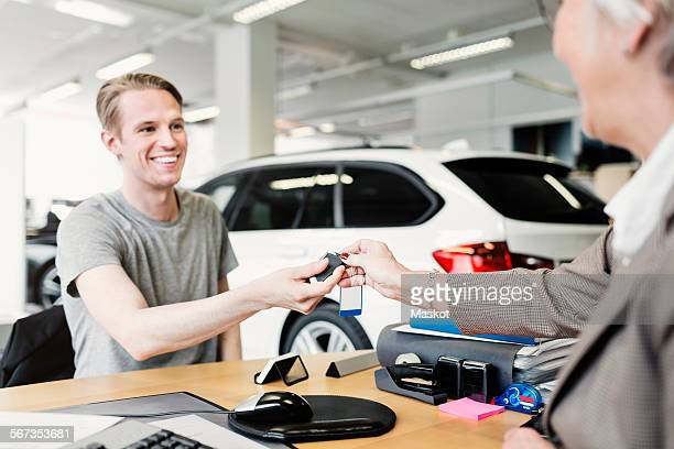 Happy man receiving car keys from saleswoman at desk in showroom