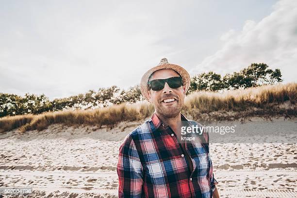 Glücklicher Mann Entspannen am Strand in Hemd und Sonnenbrille