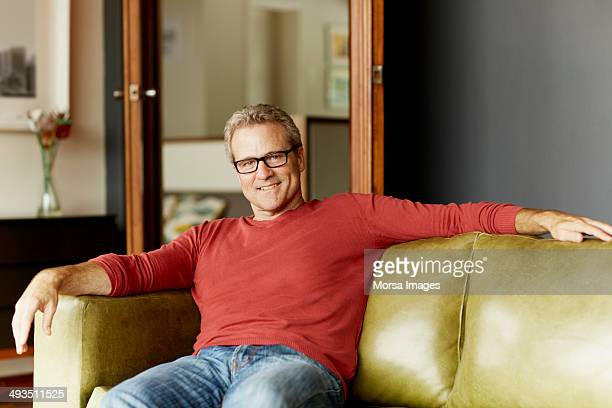 Happy man relaxing on sofa