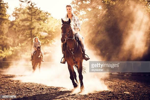 Heureux homme chevauchant un étalon au ranch.