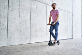 Happy man riding kick scooter