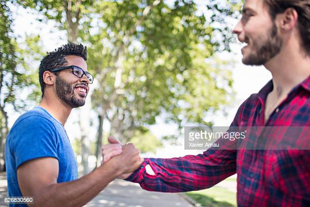 Happy man shaking hands with friend on footpath