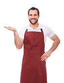 Happy man with apron showing empty copyspace on white background