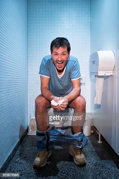 happy man sitting in public restroom