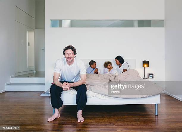 Happy man sitting on bed with family in background