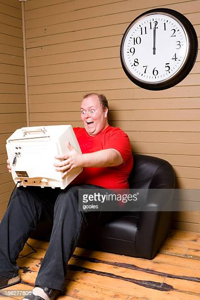 Happy Man Sitting on Couch and Holding Television