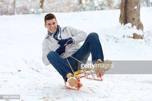 Happy man sledging downhill on a snow.