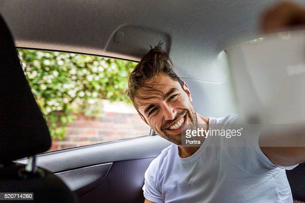 Happy man taking selfie on mobile phone in car