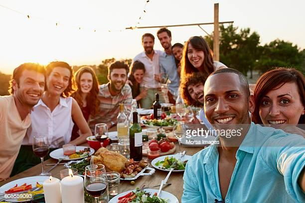 Happy man taking selfie with friends