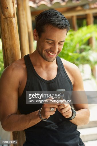 Happy man text messaging on cell phone : Stock Photo