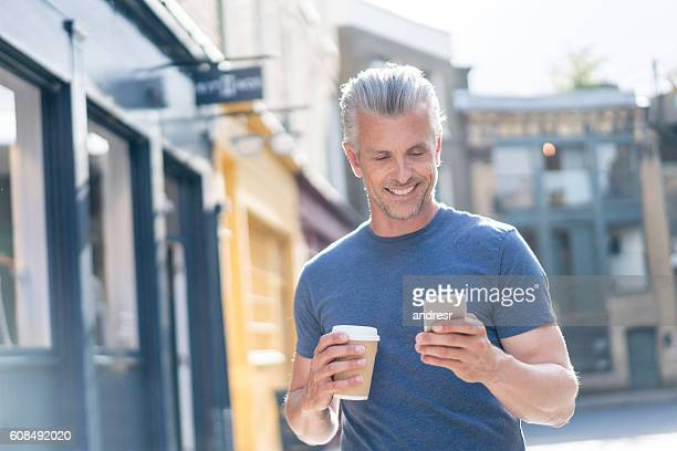 Happy man using his cell phone outdoors