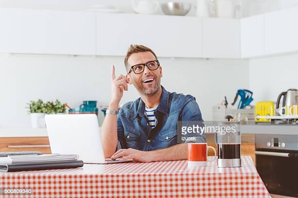 ハッピーな男性の台所でラップトップ